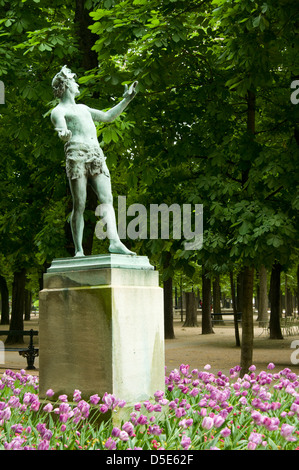 Spring flowers surround the bronze statue L'acteur Grec by Arthur Bourgeois (1838-1886) in Luxembourg Gardens, Paris, - Stock Photo