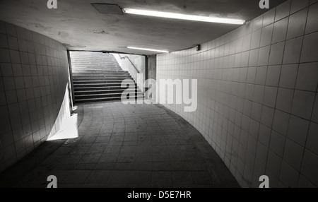 Underground passage with lights and stairs in the glowing end - Stock Photo