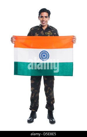 Portrait of an army soldier holding Indian flag and smiling - Stock Photo