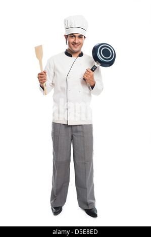 Portrait of a male chef holding a frying pan with spatula and smiling - Stock Photo