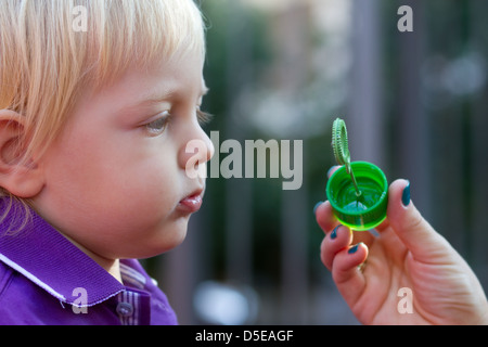 Little boy playing with his mother on the playground. Blowing bubble - Stock Photo