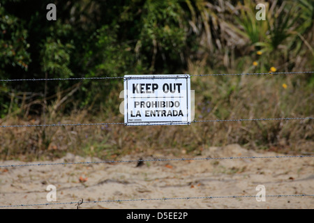 a sign on a barbed wire fence that says KEEP OUT and Prohibido la entrada in spanish - Stock Photo