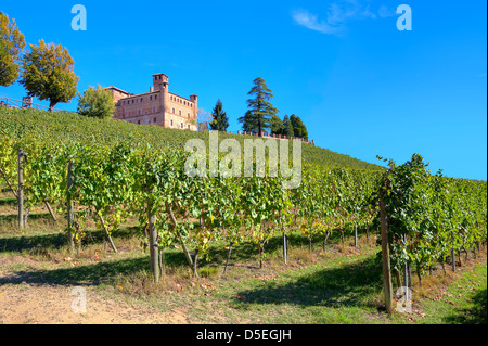 Medieval castle of Grinzane Cavour among vineyards on the downhill under clear blue sky in Piedmont, Northern Italy. - Stock Photo