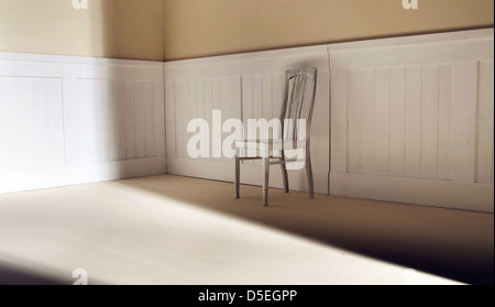 Bright interior with old chair against wall - Stock Photo