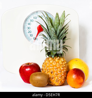 Fruits isolated on white with weight scale on the background / concept of fruit dieting and healthy lifestyle - Stock Photo
