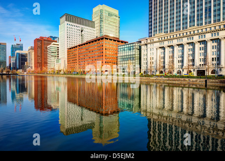 Landmark buildings reflect off the Imperial Palace moat in the Marunouchi district of Tokyo, Japan. - Stock Photo
