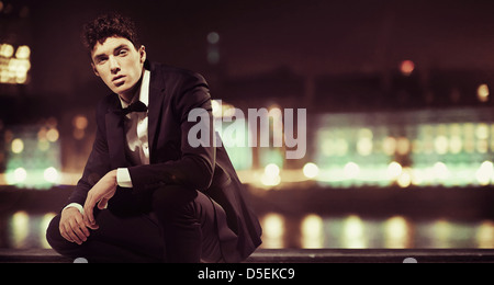 Stylish young man with night town over the background - Stock Photo