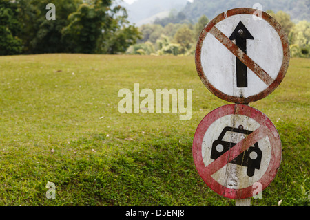 Traffic sign in front of the green field - Stock Photo