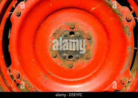 farm old tractor wheel detail red metal background - Stock Photo
