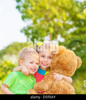 Two happy children enjoying big brown soft bear outdoors, brother and sister hugging, having fun on spring time - Stock Photo