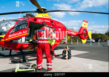 Midlands Air Ambulance landed in the car park at Hereford Hospital. Air ambulance paramedic stowing the stretcher - Stock Photo