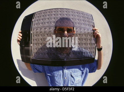 Fisheye shot of a man holding transparent electric circuit board - Stock Photo