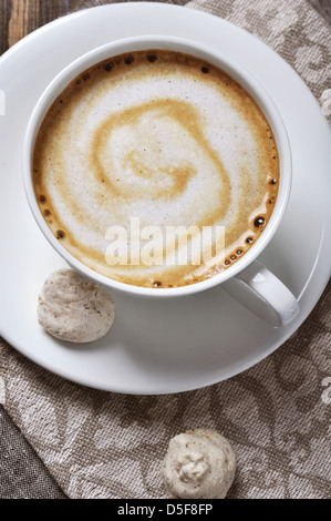 Cup of coffee with almond biscotti over wooden background - Stock Photo