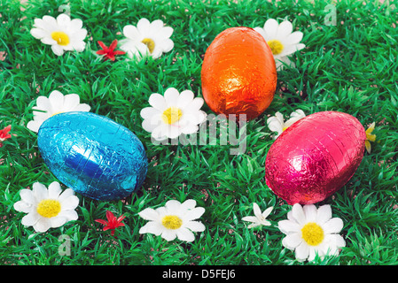 Chocolate Easter eggs on some green grass with daisies - Stock Photo