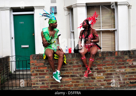 Two performers talking while they are waiting to join their float to start. Notting Hill Carnival. London, UK - Stock Photo