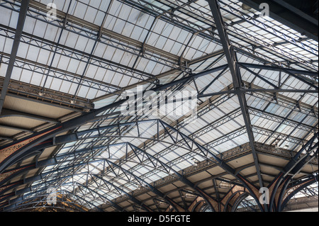 Intricate cast iron glazed Victorian engineering and detail of roof at Liverpool street station with concourse beneath - Stock Photo