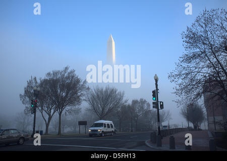 The Washington Monument peaks out through early morning fog in Washington, DC, USA - Stock Photo