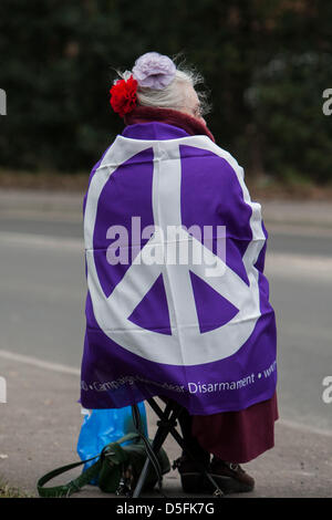 Aldermaston, UK. 1st April 2013.  Woman draped in CND flag outside an entrance to Aldermaston. Campaign for Nuclear - Stock Photo