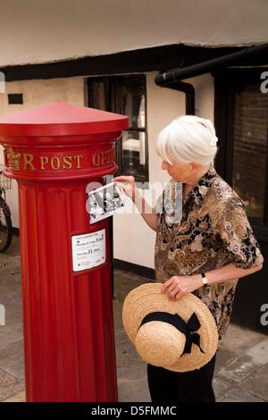 England, Berkshire, Eton High Street, tourist posting Royal postcard in historic1856 Victorian post pillar box - Stock Photo