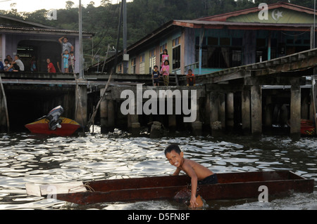 Boy paddling in front of Kampong Ayer - the worlds largest Water Village - Stock Photo