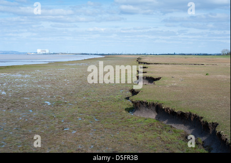 View of decommissioned Oldbury Nuclear Power Station along the eroded banks of the tidal River Severn in South Gloucestershire - Stock Photo