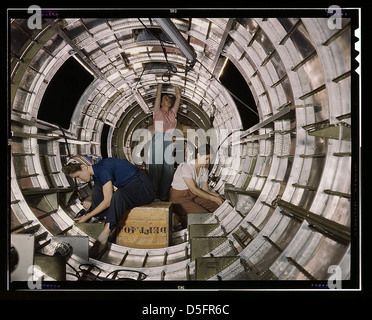 Women workers install fixtures and assemblies to a tail fuselage section of a B-17F bomber at the Douglas Aircraft - Stock Photo