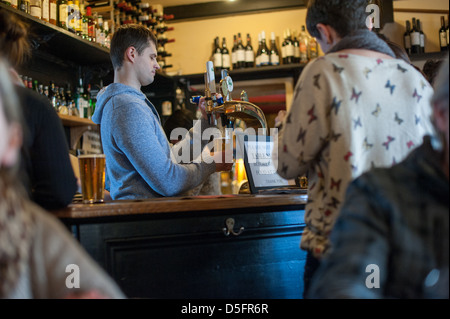 Young white barman pulling a pint of beer in an English country pub on a winter's day with drinks on the bar - Stock Photo