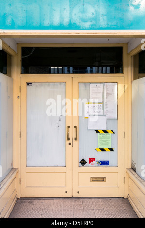 Empty shop with white washed windows and posters and notices on the door - Stock Photo