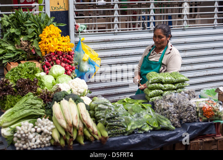 Mature Mexican woman selling fruits and vegetables in a market in Queretaro, Mexico. - Stock Photo
