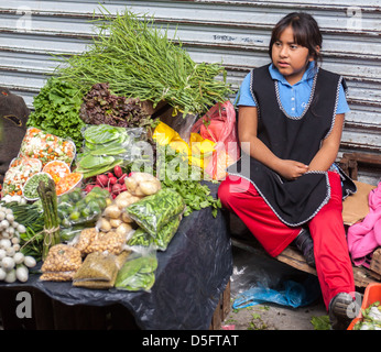 young mexican girl selling fruits and vegetables in a market in queretaro mexico