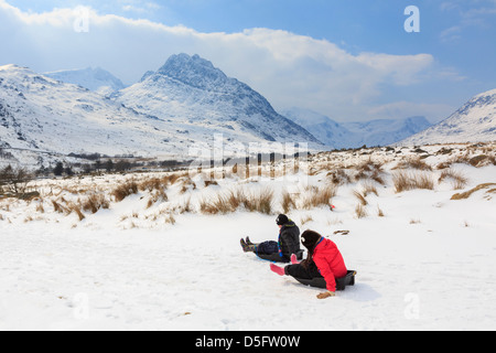 Children sledging in mountains of Snowdonia National Park during cold weather and heavy snowfall. Ogwen Valley, - Stock Photo