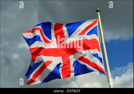 UNION JACK FLAG FLYING IN THE WIND WITH DRAMATIC SKY BEHIND - Stock Photo
