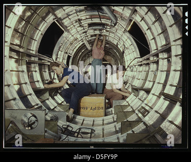 Women workers install fixtures and assemblies to a tail fuselage section of a B-17 bomber at the Douglas Aircraft - Stock Photo