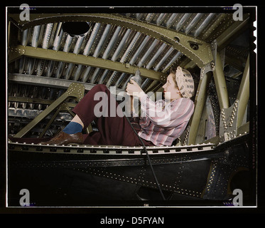 An A-20 bomber being riveted by a woman worker at the Douglas Aircraft Company plant at Long Beach, Calif. (LOC) - Stock Photo