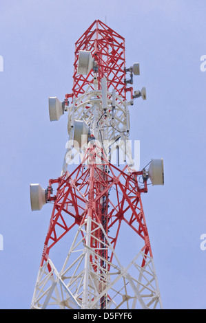 Telecommunication tower antenna with many microwave dishes for microwave transmission painted in red and white signal - Stock Photo