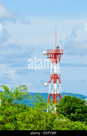 Telecommunication tower antenna with microwave dishes for microwave transmission and radar painted in red and white - Stock Photo