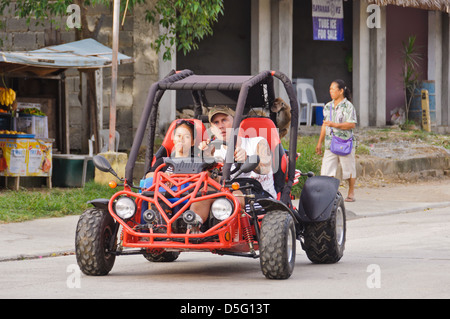 Street scene. Puerto Galera, Philippines, Asia. Interracial couple and little monkey in a off road beach buggy - Stock Photo