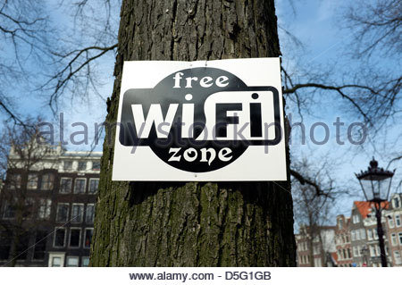 Sign on a tree 'Free Wi Fi Zone', in Amsterdam, the Netherlands. - Stock Photo