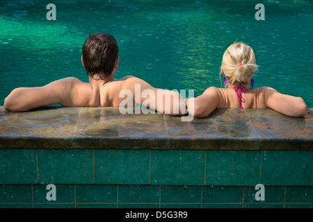 Back view of couple relaxing in a swimming pool on a poolside in tropical resort - Stock Photo