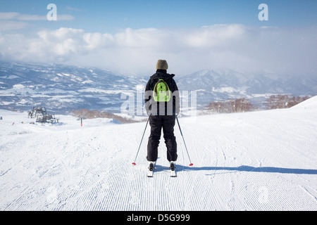 Back view of a female skier as she sets off down a freshly groomed ski slope in the light snow. - Stock Photo