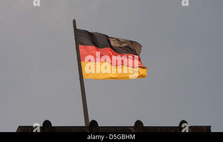 The german flag blows in the wind on top of one of the towers of the German Reichstag building in Berlin, Germany, - Stock Photo