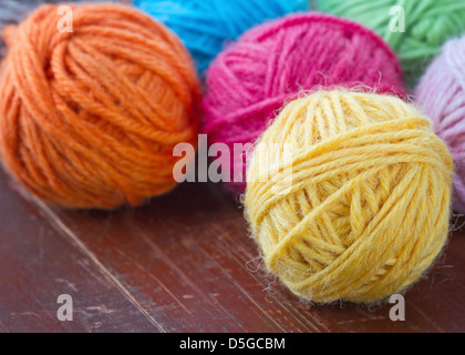 Closeup of colorful woolen yarn on old vintage wooden background - Stock Photo