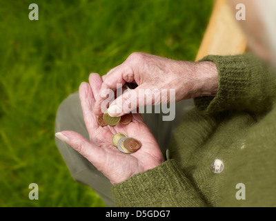 hands of a senior counting less money, poverty - Stock Photo