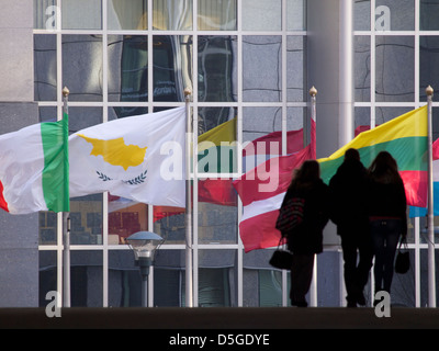 Various EU member state flags in Brussels, Belgium with silhouetted group of people walking - Stock Photo