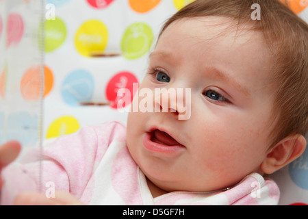 Eight month old baby girl wearing pink romper suit pictured in her high chair on her first Easter. - Stock Photo