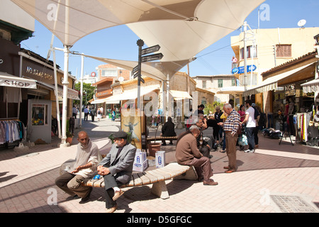 Turkish Cypriot men sitting outside in one of the street bazaars, Nicosia North, Turkish Republic of Northern Cyprus - Stock Photo