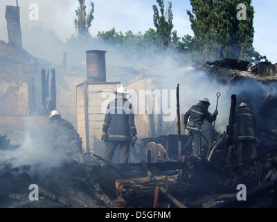Smoldering remains of a ghetto house with a fireman spraying water firefighters extinguish a fire in an apartment - Stock Photo