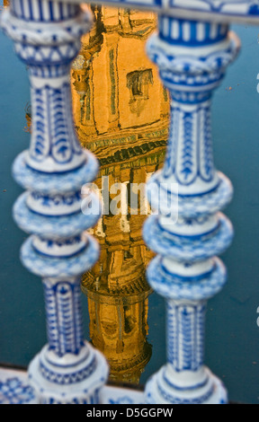 Tower reflection in water between ceramic balustrades Plaza Espana Seville Andalusia Andalucia Spain Europe - Stock Photo