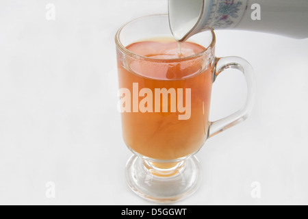 Close up jug of milk being poured into tea made in a glass tumbler - Stock Photo