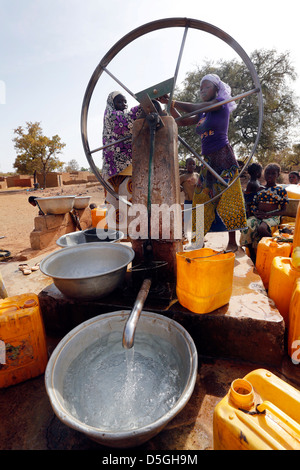 Women turn the wheel of a water pump in a village, Burkina Faso, Africa - Stock Photo